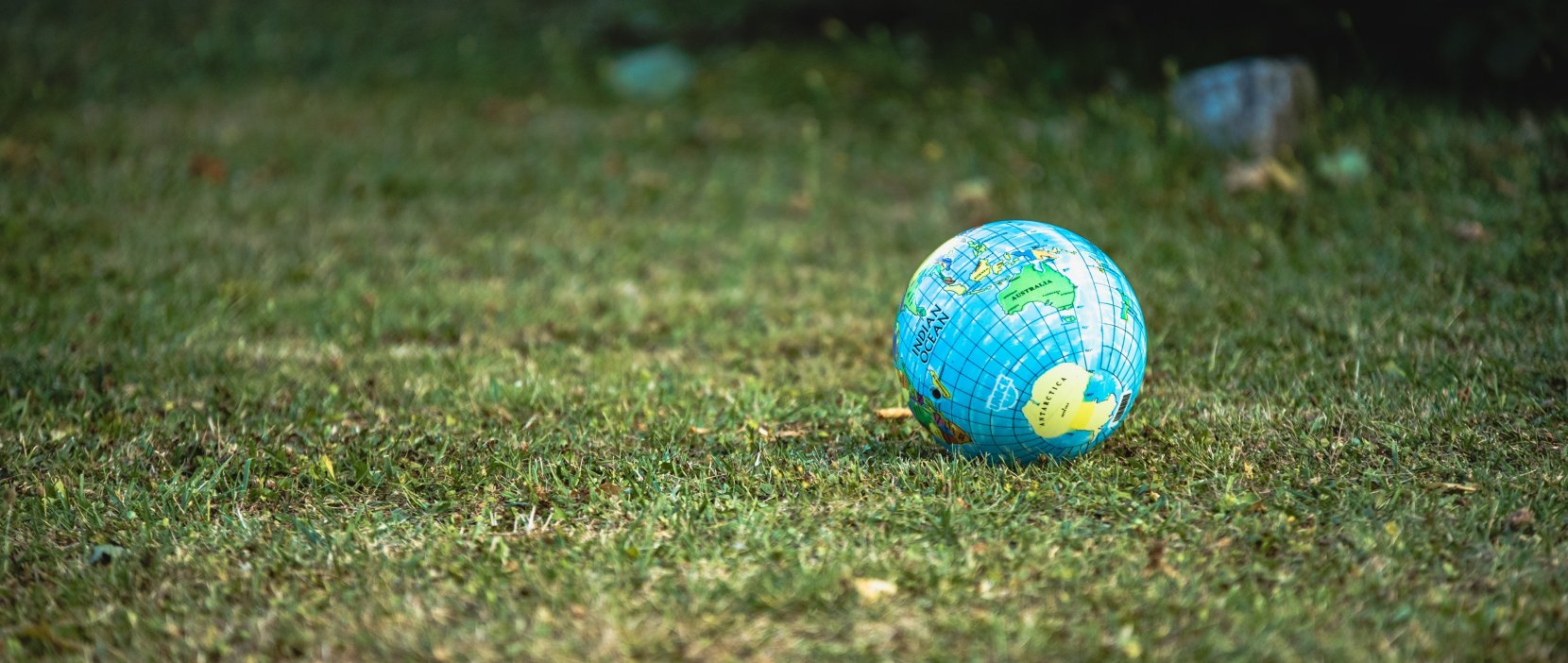 Lille globus på en stor, grøn græsplæne